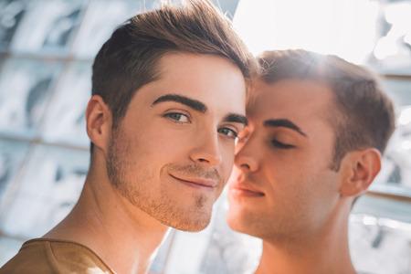 Photo pour Portrait of an affectionate young gay couple standing close together at home - image libre de droit