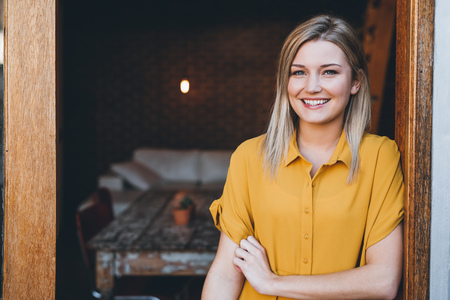 Photo pour Portrait of an attractive young blonde woman smiling while standing at the door to her modern loft apartment - image libre de droit