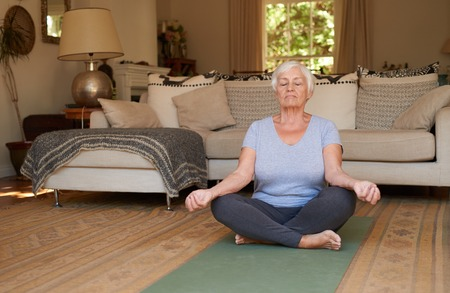 Photo for Senior woman sitting in the lotus position meditating at home - Royalty Free Image