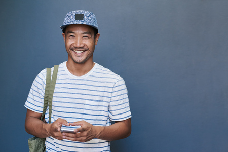 Photo pour Smiling young Asian man using a cellphone outside - image libre de droit