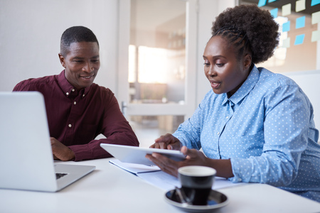 Photo for Young African businesspeople using technology together in an office - Royalty Free Image