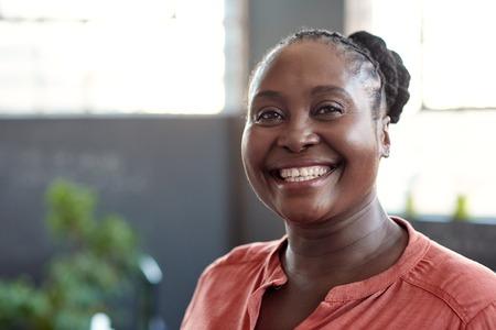 Foto für Young African businesswoman smiling confidently in an office - Lizenzfreies Bild