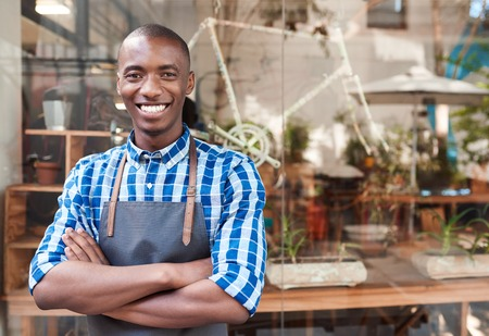 Photo for Smiling African entrepreneur standing behind a counter of his cafe - Royalty Free Image