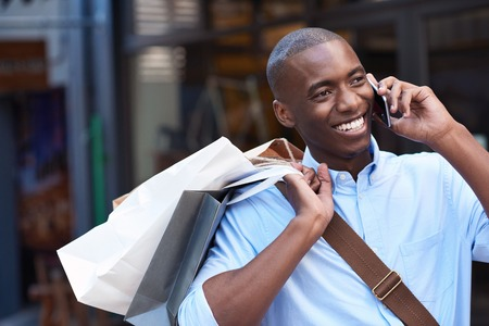 Photo for Young man carrying shopping bags talking on his cellphone outside - Royalty Free Image