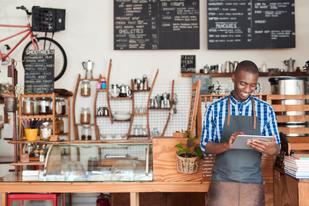 Photo for Young entrepreneur standing in his cafe using a digital tablet - Royalty Free Image