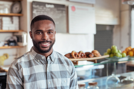 Photo pour Smiling young African entrepreneur standing in his cafe - image libre de droit