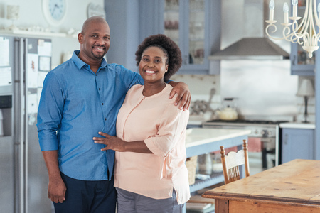 Foto de Smiling African couple standing together in their kitchen - Imagen libre de derechos