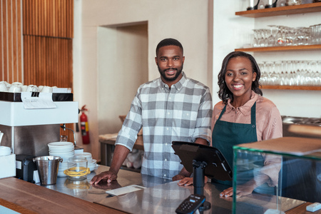 Photo for Smiling African entrepreneurs standing at the counter of their bakery - Royalty Free Image