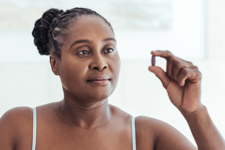 Foto de African woman looking at a pill in her hand - Imagen libre de derechos
