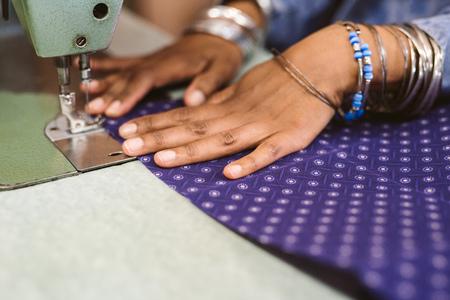 Foto de Closeup of a seamstress stitching cloth with her sewing machine - Imagen libre de derechos
