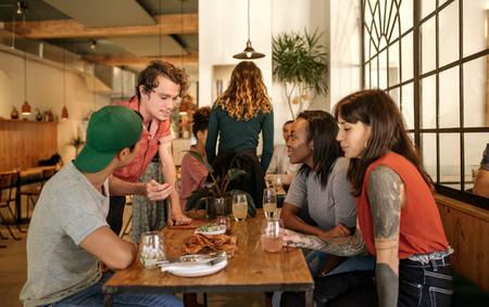 Foto de Smiling waiter talking with a group of bistro customers - Imagen libre de derechos