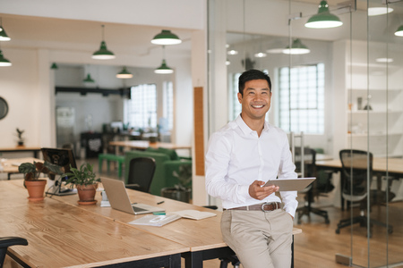Photo for Smiling Asian businessman using a tablet in an office - Royalty Free Image