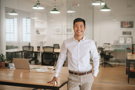 Photo for Young Asian businessman standing in an office smiling confidently - Royalty Free Image