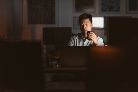 Photo pour Asian businessman drinking coffee while working late in an offic - image libre de droit