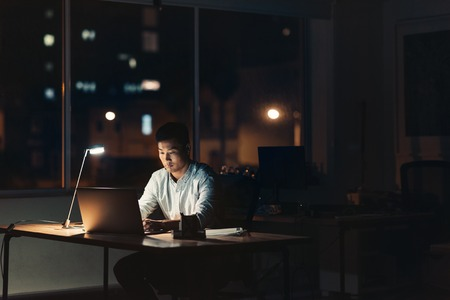 Photo for Young Asian businessman working on a laptop while sitting at his desk in a dark office at night with city lights in the background - Royalty Free Image