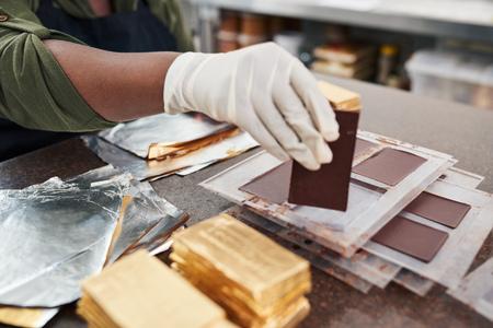 Foto de Worker wrapping chocolate bars from molds in gold foil - Imagen libre de derechos