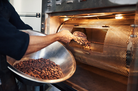 Foto de Chocolate making factory worker putting cocoa beans into a roaster - Imagen libre de derechos