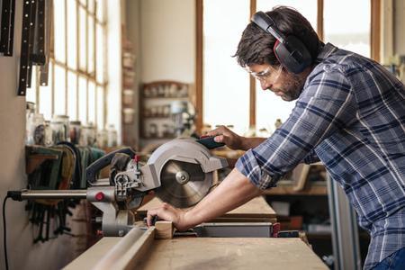 Photo pour Carpenter sawing wood with a mitre saw in his workshop - image libre de droit