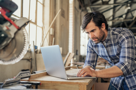Photo for Woodworker doing research on a laptop in his workshop - Royalty Free Image