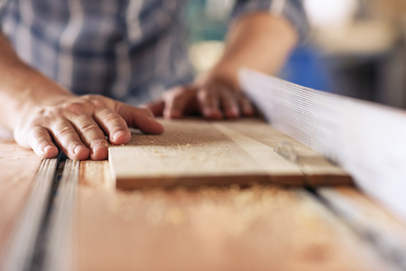 Photo pour Woodworker sawing planks of wood in his carpentry workshop - image libre de droit