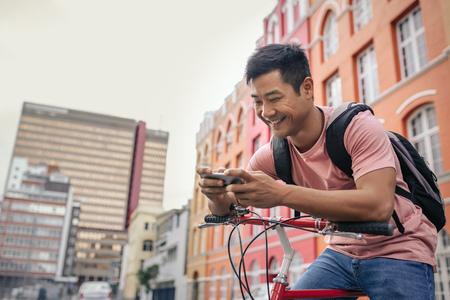 Foto de Smiling young man sitting on his bike sending a text - Imagen libre de derechos