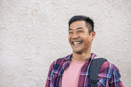 Photo pour Young Asian man standing on a city street laughing - image libre de droit