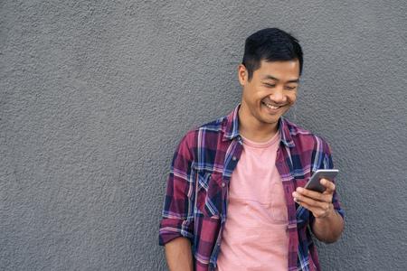 Foto de Smiling young Asian man reading a text on his cellphone - Imagen libre de derechos