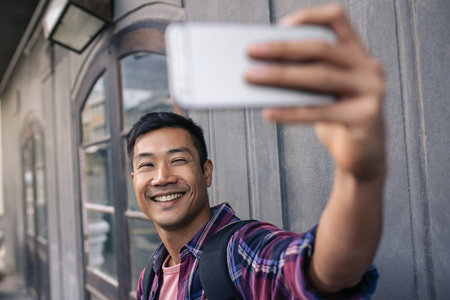 Foto de Young Asian man smiling while taking selfies outside - Imagen libre de derechos
