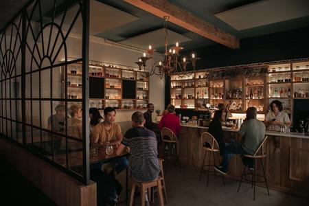 Foto de Diverse people enjoying drinks at a bar in the evening - Imagen libre de derechos
