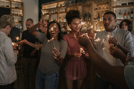Photo for Laughing friends celebrating with sparklers in a bar at night - Royalty Free Image