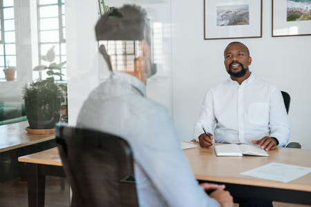 Photo for Smiling manager interviewing a potential employee in his office - Royalty Free Image