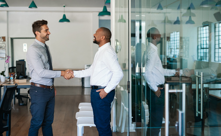 Photo for Two laughing businessmen shaking hands together after an office meeting - Royalty Free Image