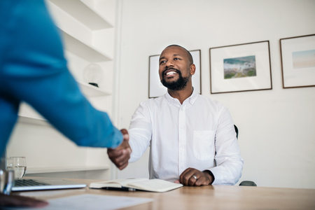 Photo for Smiling manager shaking hands with an employee in his office - Royalty Free Image