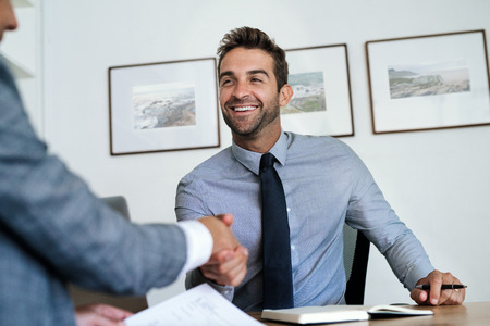 Photo for Manager sitting at his desk shaking hands with an employee - Royalty Free Image