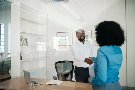 Photo for Manager standing in his office shaking hands with an employee - Royalty Free Image