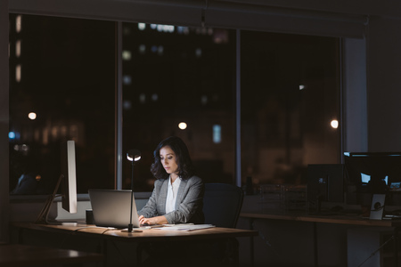 Foto de Young businesswoman working online in a dark office at night - Imagen libre de derechos