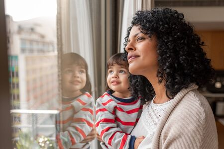 Photo for Mother and cute daughter looking through a window at home - Royalty Free Image