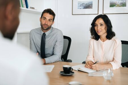 Photo for Two young businesspeople talking with a colleague in an office - Royalty Free Image