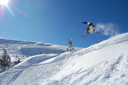 Snowboarder jumping from a cliff in snow powder  Ukraine, Carpathians, Dragobrat