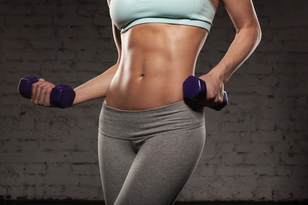 Foto de Fitness female woman with muscular body, do her workout with dumbbells, abs, abdominals - Imagen libre de derechos