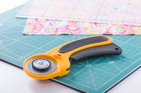 Photo for Rotary cutter on plan front on green mat - Royalty Free Image