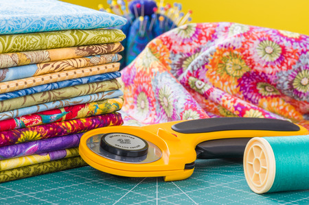 Photo for Rotary cutter and spool of thread on a background fabric - Royalty Free Image