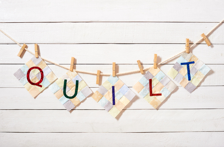 Foto de Sewn letters, ?ombined as the word quilt, attached with clothespins on a rope on a white wooden background - Imagen libre de derechos