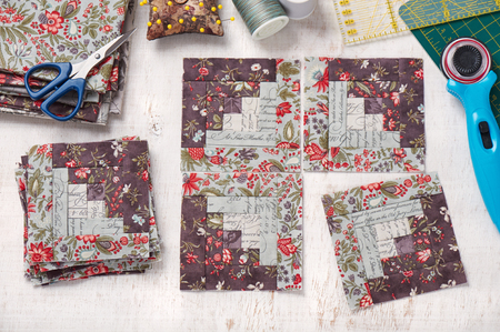 Photo pour Patchwork log cabin blocks, stack of blocks, sewing accessories on white wooden surface - image libre de droit
