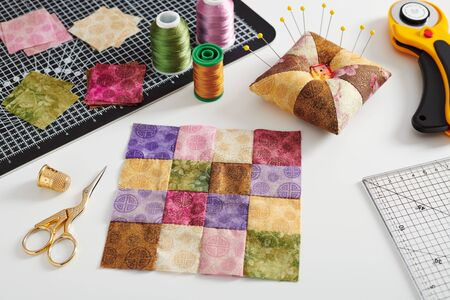 Photo for Quilting block from bright square pieces of fabrics, pincushion, stacks of square pieces of fabrics, quilting and sewing accessories - Royalty Free Image