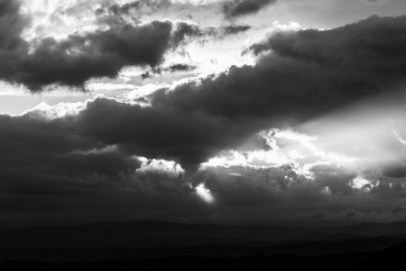 Photo for Sunset over a valley with sun rays coming out through some clouds - Royalty Free Image