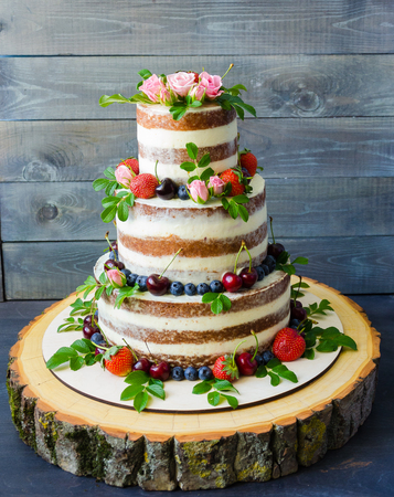 Photo pour Naked wedding cake decorated with berries and flowers - image libre de droit