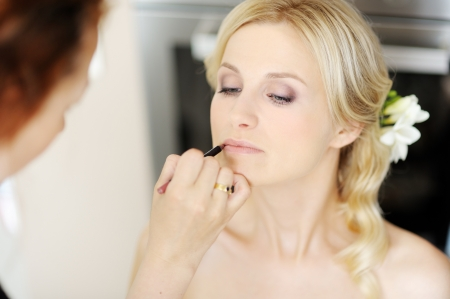 Photo for Young beautiful bride applying wedding make-up by make-up artist - Royalty Free Image