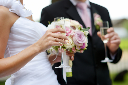 Photo pour Bride is holding a wedding bouquet and a glass of champagne - image libre de droit