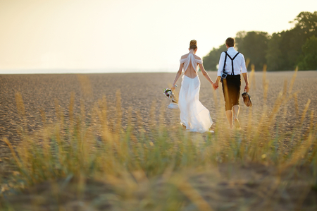 Photo for Happy bride and groom on a beautiful beach on sunset - Royalty Free Image